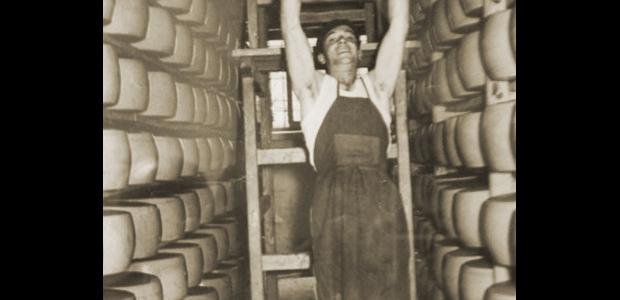 Divino Benassi solleva due forme di Parmigiano